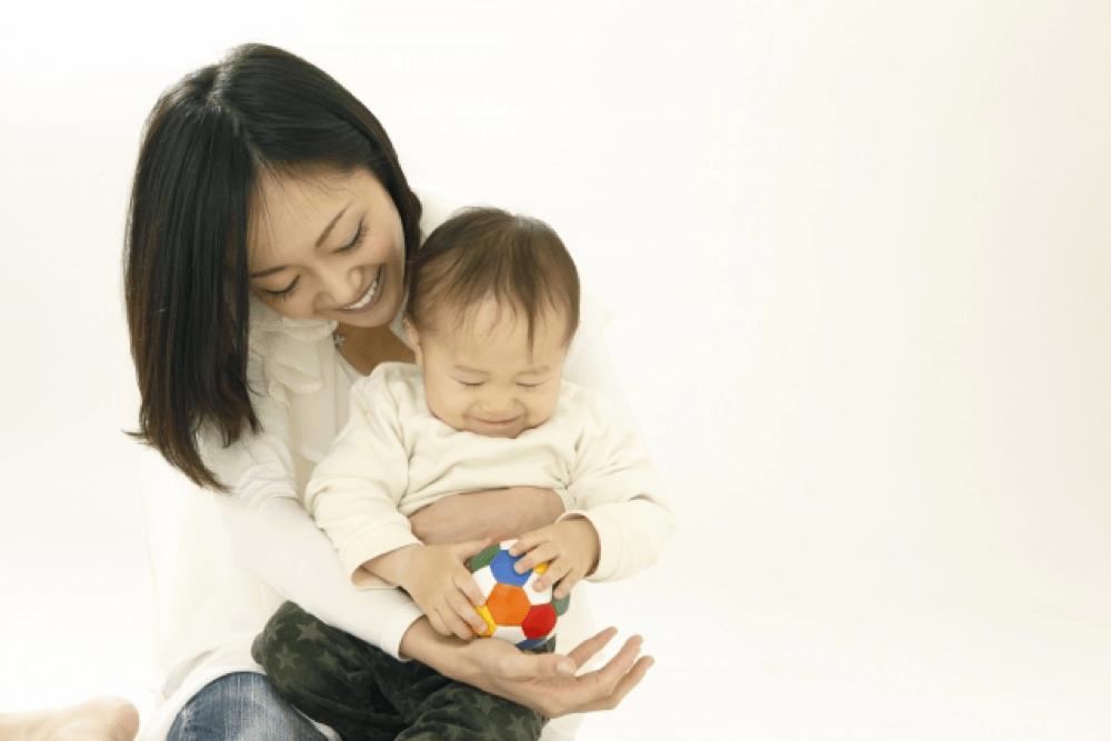 オモチャを持つ赤ちゃんを抱く女性