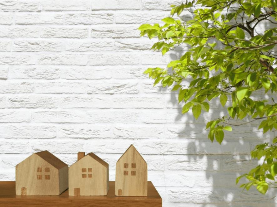 3個並ぶ家のフィギュア、白壁に緑