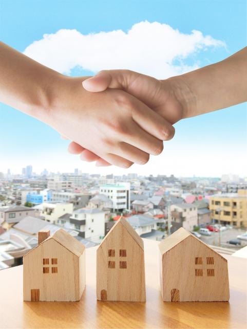 家の模型と握手する二人