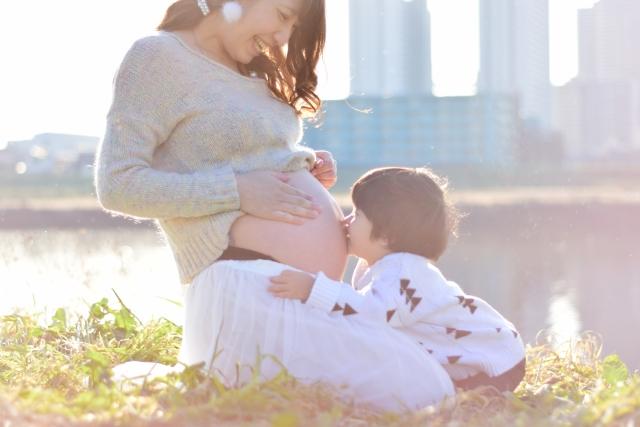 妊娠しているお母さんのお腹にキスをする子ども