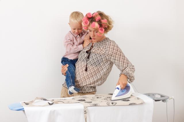 アイロンをかけながら子どもを抱っこするママ