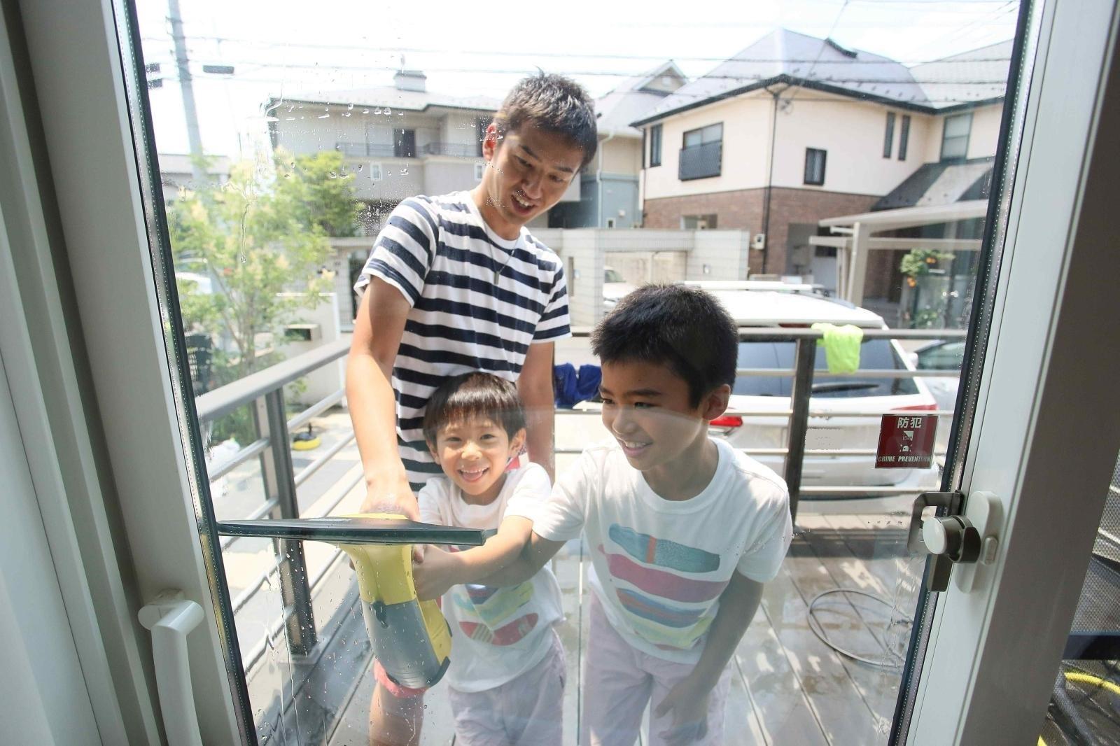 窓掃除をするお父さんと子どもたち
