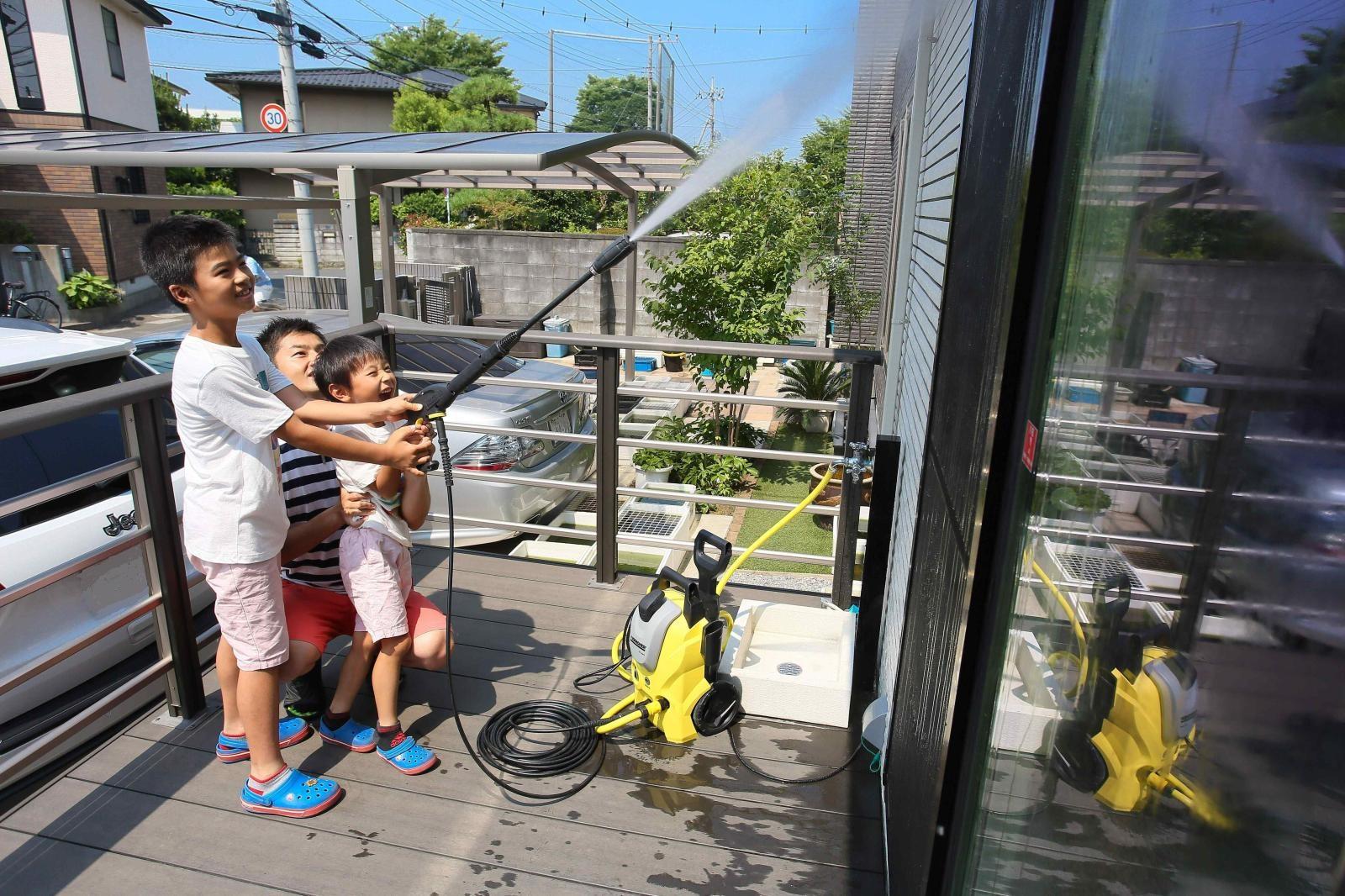 高圧洗浄機で外壁掃除をする親子