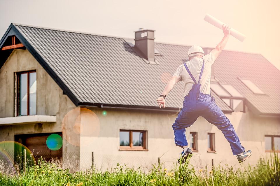 中古物件と図面をもって飛び跳ねる男性