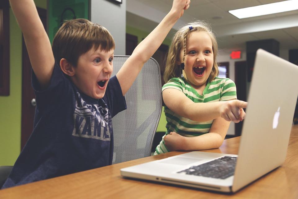 ノートパソコンの前で喜ぶ子供