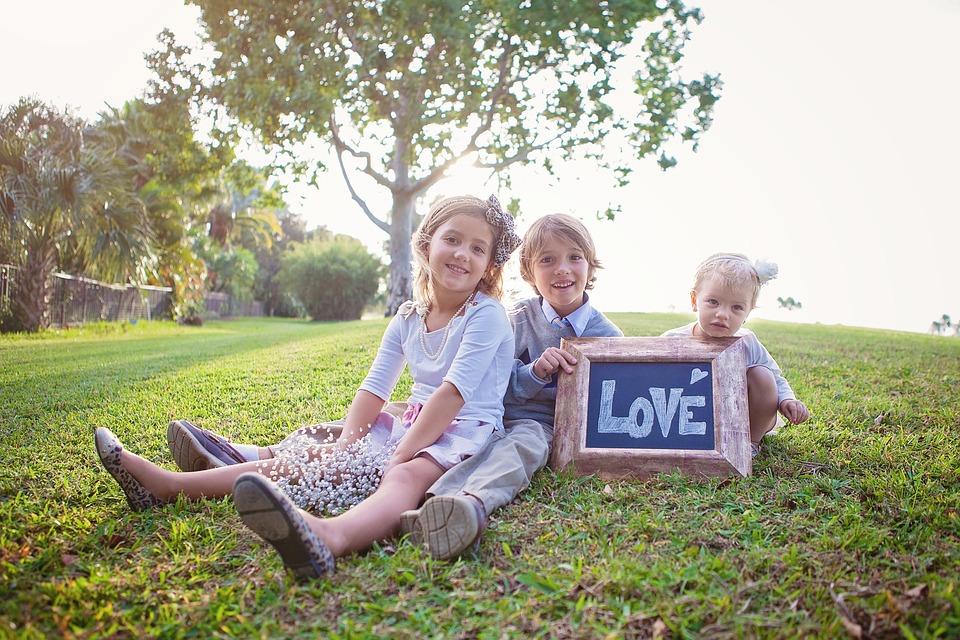 自然いっぱいの場所で座っている3人の子ども
