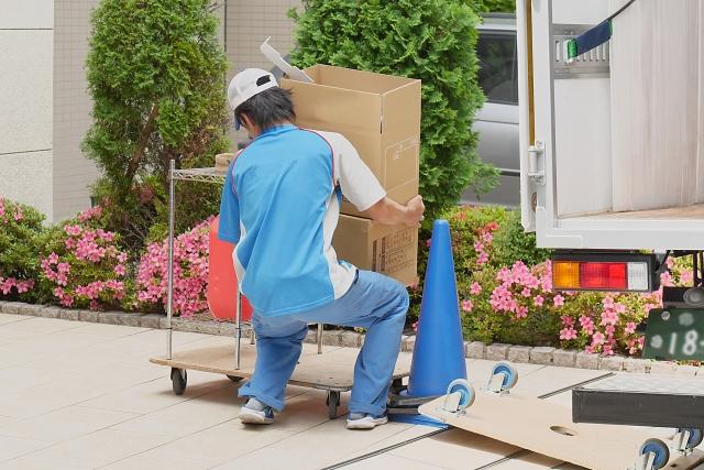 重い荷物を運ぶ引越し業者