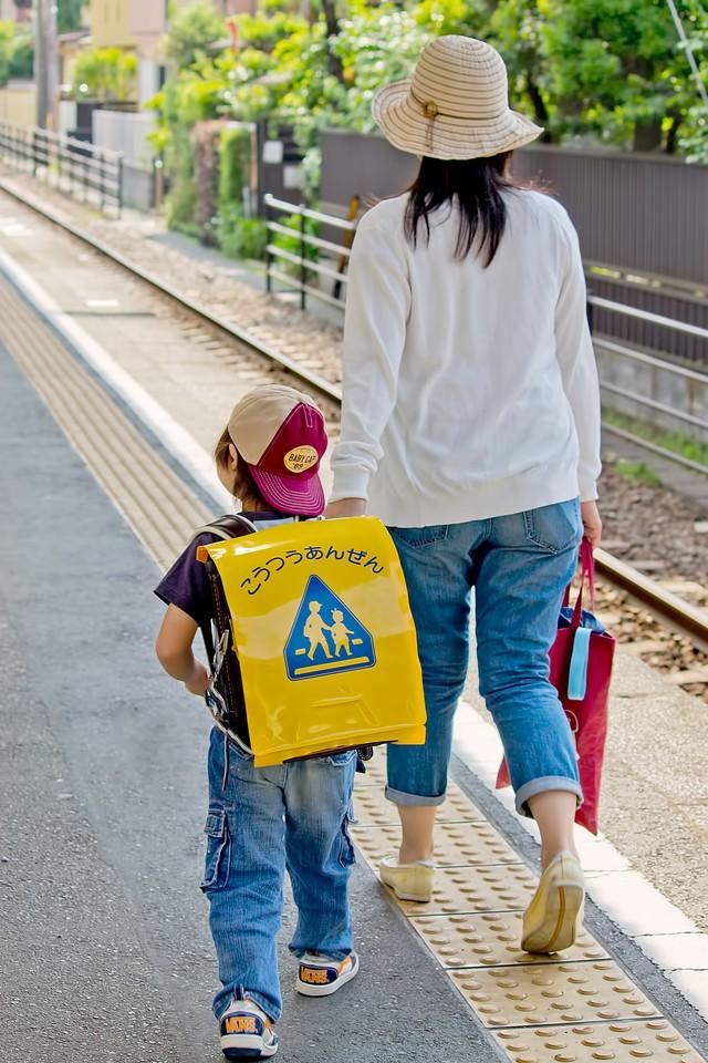 手をつないで歩く母親と子ども