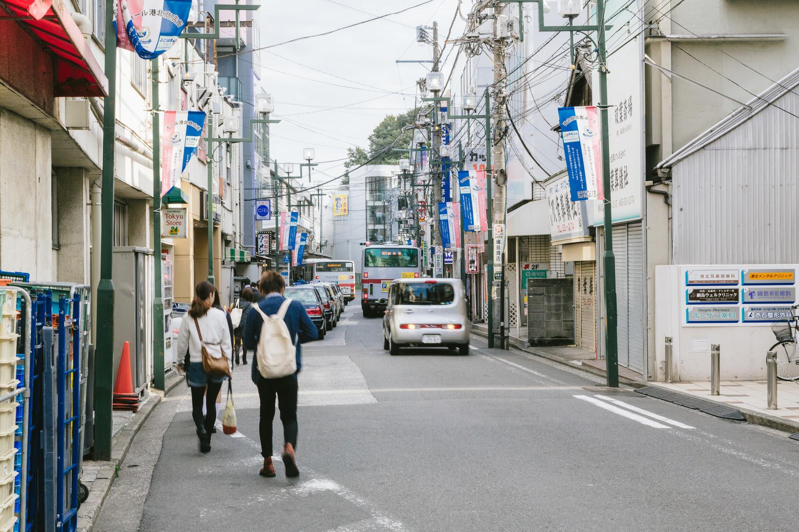 電柱がたくさんある道路を歩く人たち