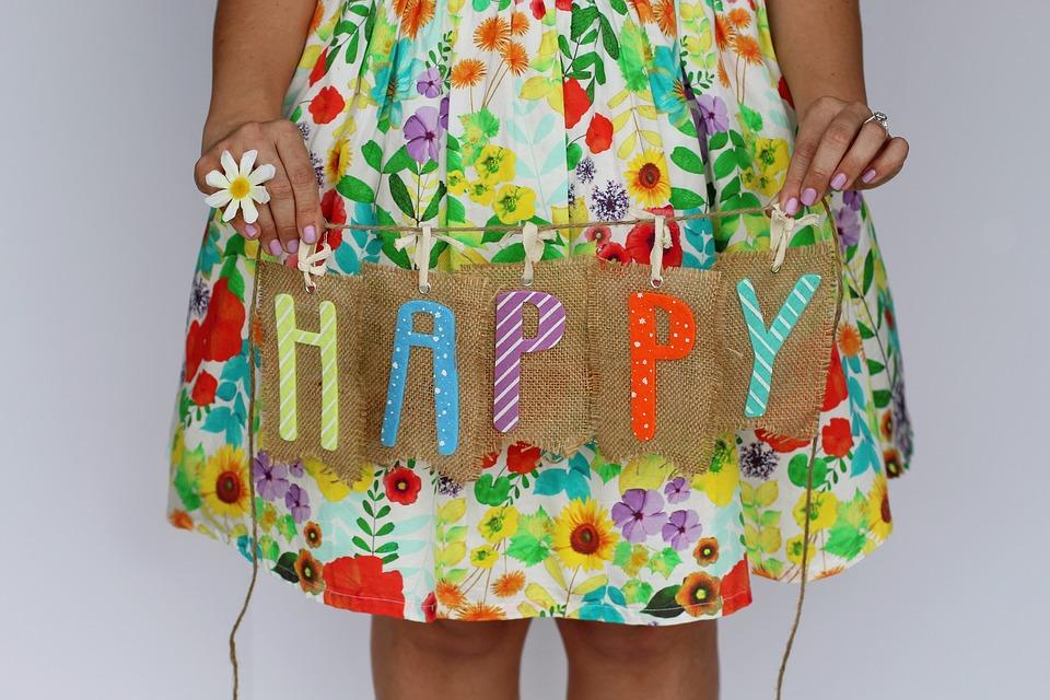 「HAPPY」と書かれたボードを持つ女の子