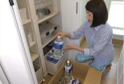 パントリーに水を収納する主婦