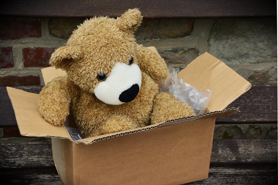 ダンボールに梱包される熊のぬいぐるみ