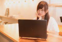 パソコンを見ながら考え込む女性