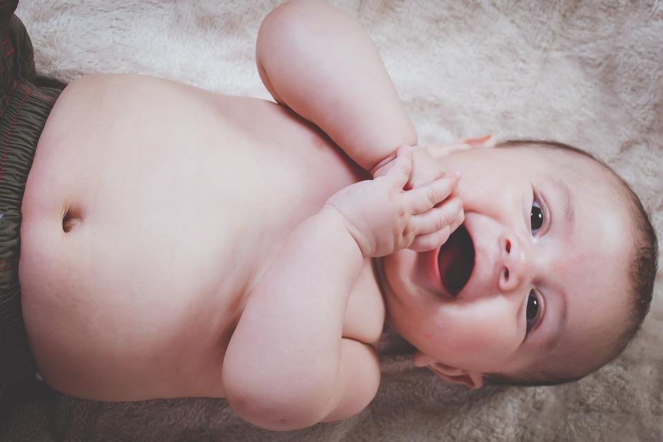 笑顔で両手を合わせる赤ちゃん