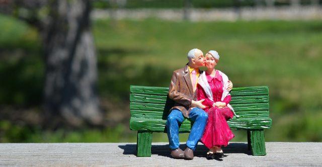 ベンチでキスする老夫婦の人形