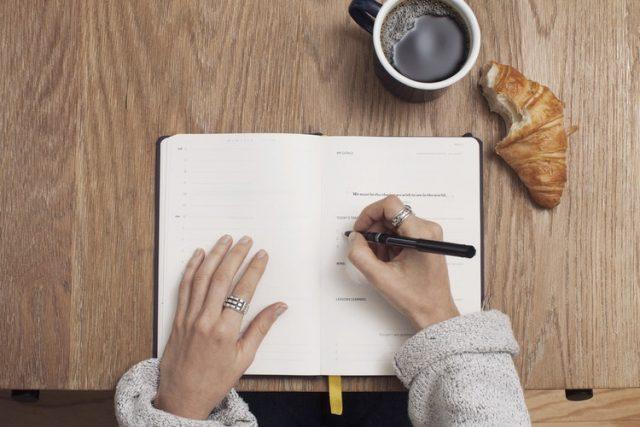 ノートに文字を書き込んでいる女性