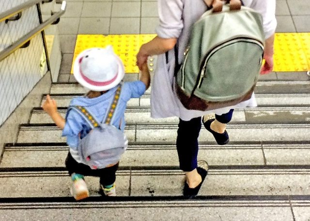 ママと手をつないで階段を降りる子ども