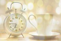 白い目覚まし時計とコーヒーカップ