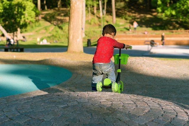 公園でスクーターに乗って遊ぶ男の子