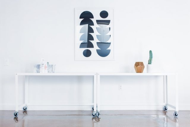 絵の掛かった白い壁と白いテーブル