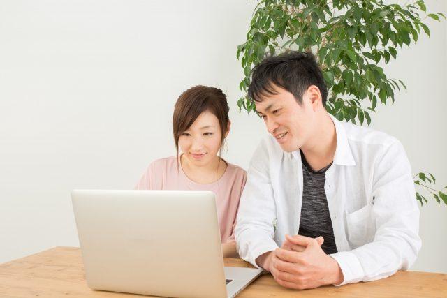パソコンの画面を見る若い夫婦