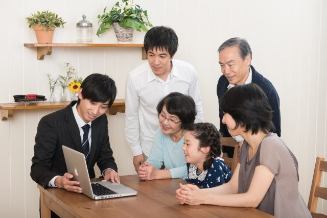 パソコンを見ながら説明を聞く家族